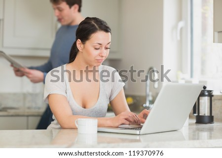 Two people are in the kitchen and reading a magazine and working on the laptop - stock photo