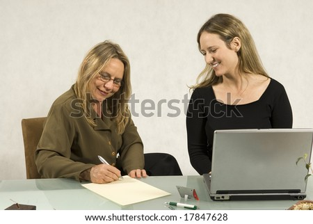 Two people are sitting together in a room at a table. The older woman is writing on a piece of paper and the younger woman is looking at the paper and smiling. - stock photo