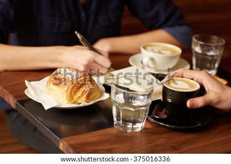 Two people at a coffee shop with one taking notes - stock photo