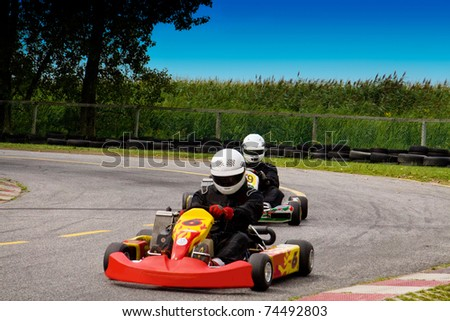 Two people competetively racing with go-karts - stock photo