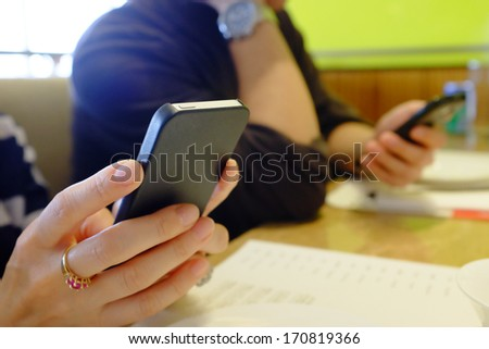 Two people doing text messaging at a restaurant table . - stock photo