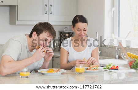 Two people eating sandwiches and drinking juice while sitting in the kitchen - stock photo