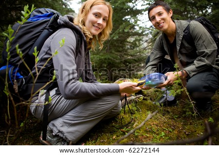 Two people finding a geocache in the forest.  Shallow depth of field with sharp focus on woman. - stock photo