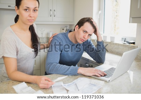 Two people focused on finances while working on the laptop in the kitchen