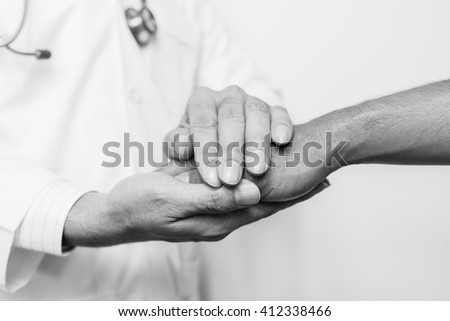 Two people holding hands for comfort , black and white. - stock photo