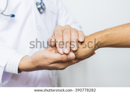 Two people holding hands for comfort. Doctor Joins Patients. Doctors wear white. Focus on hands Doctor in hotpital.  - stock photo