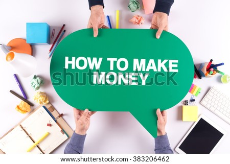 Two people holding speech bubble with HOW TO MAKE MONEY concept - stock photo