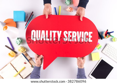 Two people holding speech bubble with QUALITY SERVICE concept - stock photo