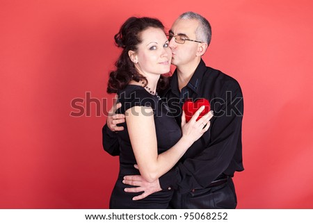Two people in love holding the heart. Studio shot. - stock photo