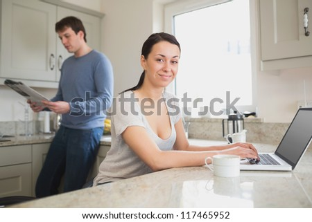 Two people in the kitchen using the laptop and reading a magazine - stock photo