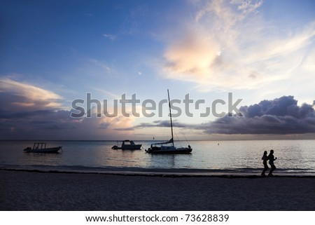 Two people jogging along the shoreline at sunrise. Punta Cana, Dominican Republic. - stock photo