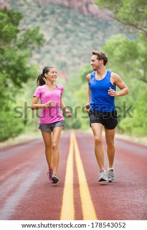 Two people jogging for fitness running on road outside in beautiful landscape nature. Woman and man sports athletes training for marathon. Couple together, Asian woman, Caucasian man, - stock photo