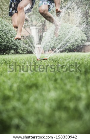 Two people jumping through a sprinkler - stock photo