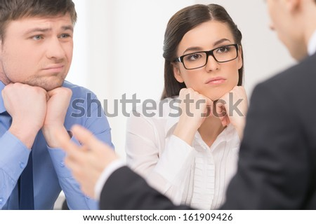 Two people listening to man. Woman with attention and man with bored face.  - stock photo