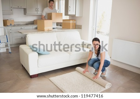Two people moving into their house and furnishing the kitchen and living room - stock photo