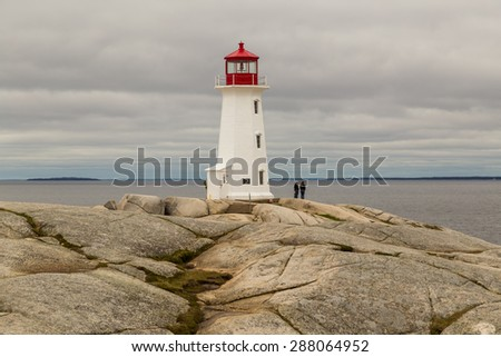 Two people on the rocky outcrop on which Peggy's Cove Lighthouse stands.  Cloudy skies over the famous landmark. - stock photo