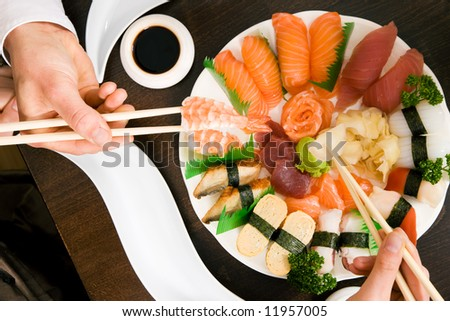 Two people (only hands to be seen) eating sushi; focus on the food - stock photo
