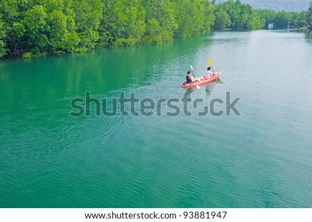 Two people paddling a kayak - stock photo