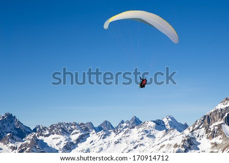 two people paragliding in tandem high in the blue sky - stock photo