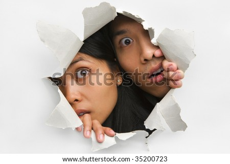 Two people peeking from hole in wall - stock photo
