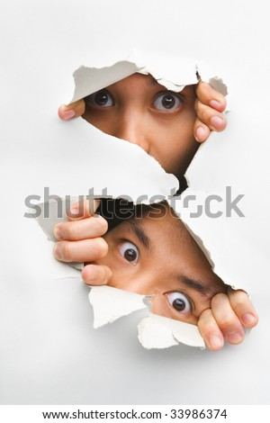 Two people peeking from hole in wall showing their eyes only - stock photo