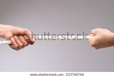 Two people playing tug of war - stock photo