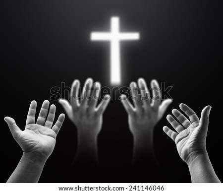 Two people pray together, focus on hands of near and blurred another one, over blurred the white cross. - stock photo