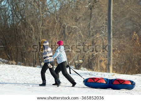 Two People Pull a Big Snow Tube. Family Vacation Snow Tubing Sport Concept - stock photo