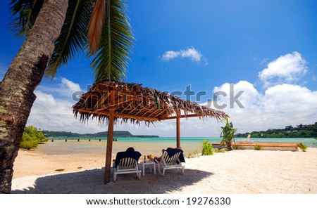 Two people relaxing under beach hut - stock photo
