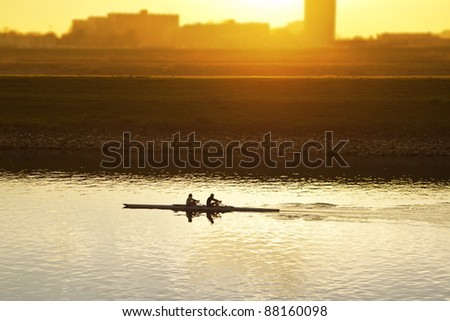 two people rowing on a river - stock photo