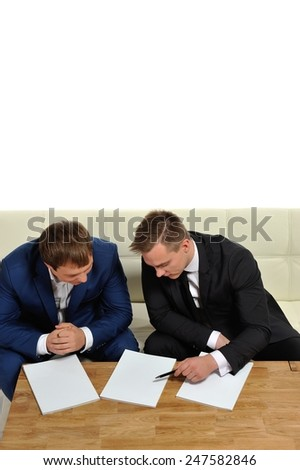 Two people sharing information. Or two business men in the negotiation process. Copy space above and magazine pages for your text. - stock photo
