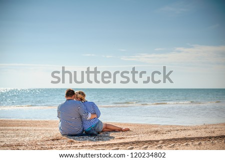 two people sitting on the beach and hugging