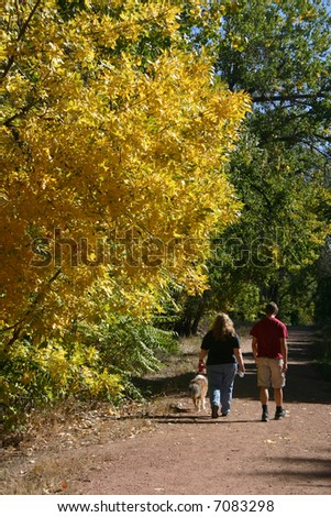 Two people taking a walk with their dog along a path surrounded by beautiful fall foliage. - stock photo
