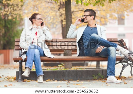 Two people talking on the phones in a park - stock photo