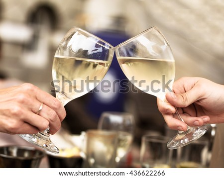 Two People Touching Glasses of White Wine Celebrating an Event or Good News - stock photo
