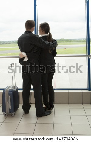 Two people waiting on a plane with suitcase - stock photo