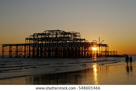 Two people walking along Brighton Beach at low tide, with the silhouette of West Pier in the background, West Sussex, UK