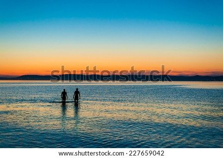 Two people walking away side by side in the beautifully rippled water refllecting the sky at  sunset