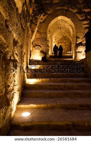 Two people walking up the stairs in the Ajlun Castle, Jordan.