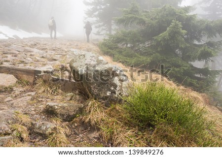 Two people wandering on the mountain in the mist
