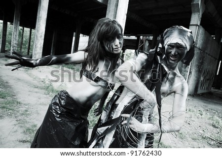 two people with creative face-art.Shooting in the destroyed building - stock photo