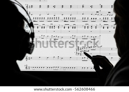 Two people working on a musical score using computer notation software. Not a real score, notes randomly drawn in by the photographer, property release for the music artwork attached.