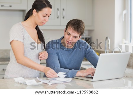 Two people working on finances and using the laptop in the kitchen - stock photo