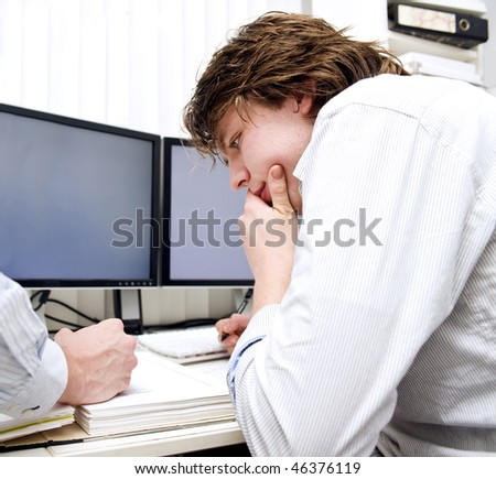 Two people, working together, concentrated examining a thick dossier, in an office environment - stock photo