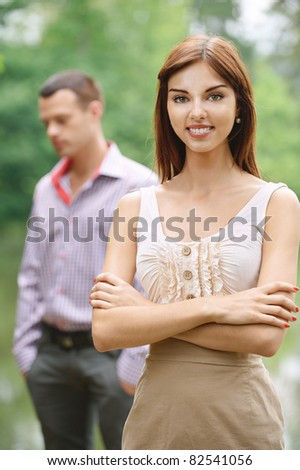 Two people: young smiling dark-haired woman wearing beige dress and young handsome man standing at summer green park. - stock photo