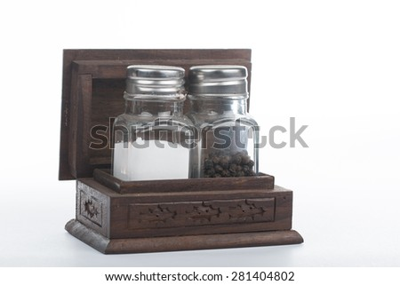 Two pepper bottles on wood box - stock photo