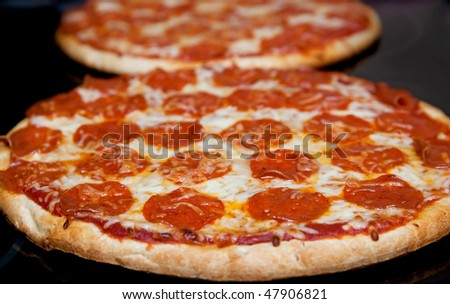 two pepperoni pizzas in a line on a black stove surface low angle - stock photo