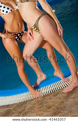 Two perfect young girls relaxing on water pool border - stock photo