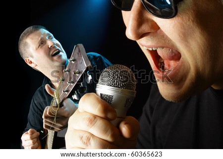 Two performers with microphone and guitar over black background - stock photo