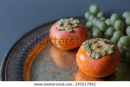 Two persimmons and a bunch of green grapes on an antique silver platter.  - stock photo